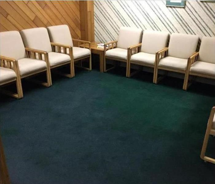Waiting room with chairs lined against wall and wet green carpet