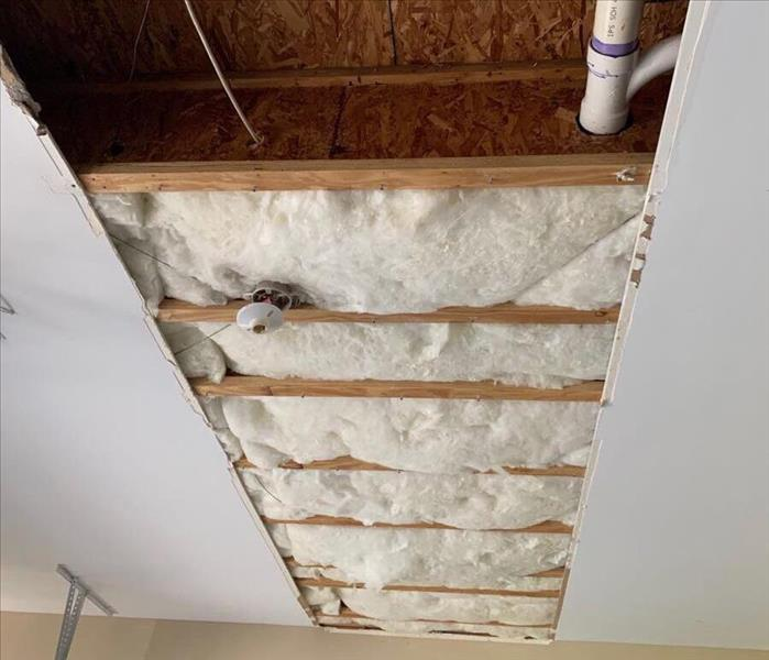 Cut out celing showing stids and wet insulation