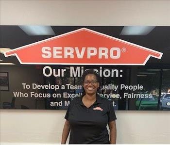 Jenea posing in front of Serpvo sign and mission statement.