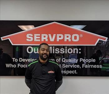 Marquise in front of our SERVPRO mission sign, wearing a black SERVPRO polo.
