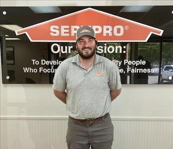 Guy standing in front of SERVPRO mission sign with a grey SERVPRO logo shirt and grey and white SERVPRO logo hat