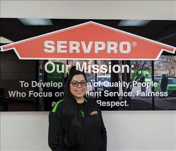 Brenda in front of our SERVPRO mission sign, wearing a black SERVPRO polo.