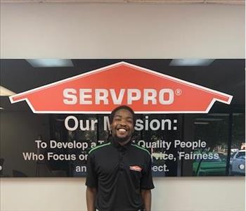 Justin in front of our SERVPRO mission sign, wearing a black SERVPRO polo.