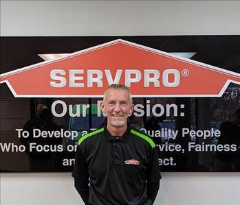 Scott in front of our SERVPRO mission sign, wearing a black SERVPRO polo.
