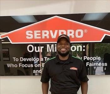 Lamar posing in front of SERVPRO sign and mission statement.