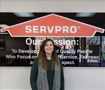 Sarah in front of our SERVPRO mission sign, wearing a black SERVPRO polo.