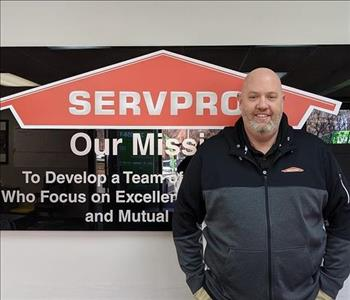 Thomas in front of our SERVPRO mission sign, wearing a black SERVPRO sweathshirt.