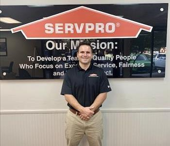 guy standing in front a SERVPRO mission sign with a black SERVPRO logo shirt
