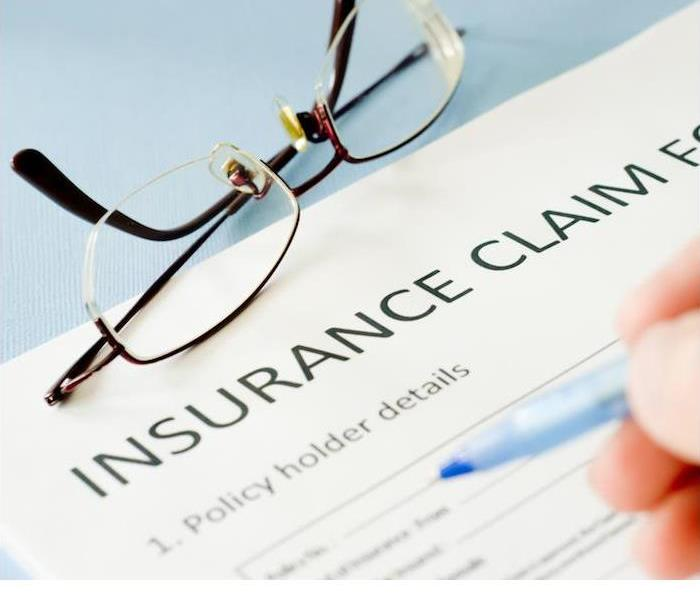 insurance claim document and reading glasses sitting on blue desk